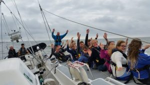 Young people sailing and waving onboard Challenge Wales Tall Ship